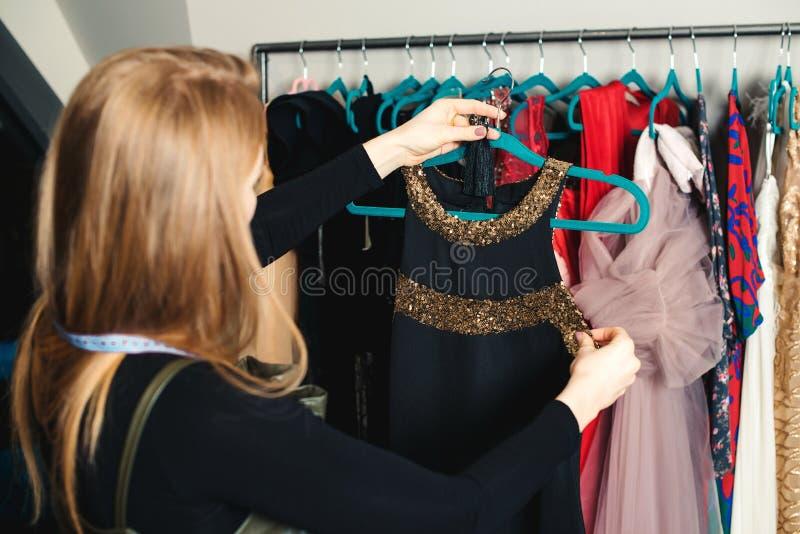 Fashion girl kiest een jurk voor een avondfeest Vrouwelijke kleermaker met kleerhanger Vrouw die in modeboutique werkt royalty-vrije stock afbeeldingen