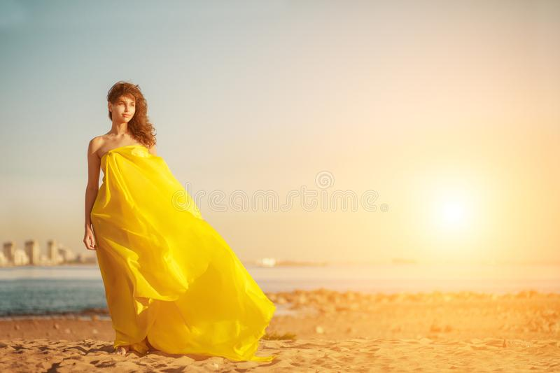 Fashion girl in a long dress against a summer sunset background. A beautiful model on the beach sand near the water in a dress flying in the wind. Luxurious stock photos