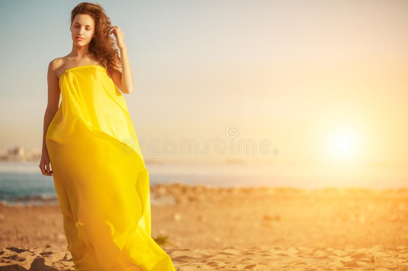 Fashion girl in a long dress against a summer sunset background. A beautiful model on the beach sand near the water in a dress flying in the wind. Luxurious royalty free stock images