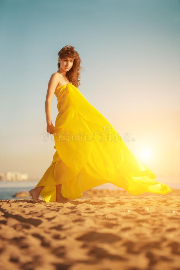 Fashion girl in a long dress against a summer sunset background. A beautiful model on the beach sand near the water in a dress flying in the wind. Luxurious stock image