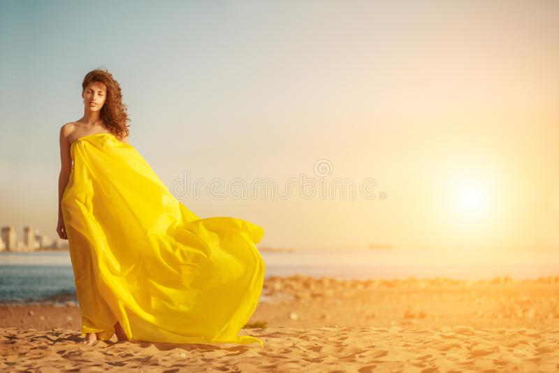 Fashion girl in a long dress against a summer sunset background. A beautiful model on the beach sand near the water in a dress flying in the wind. Luxurious stock images