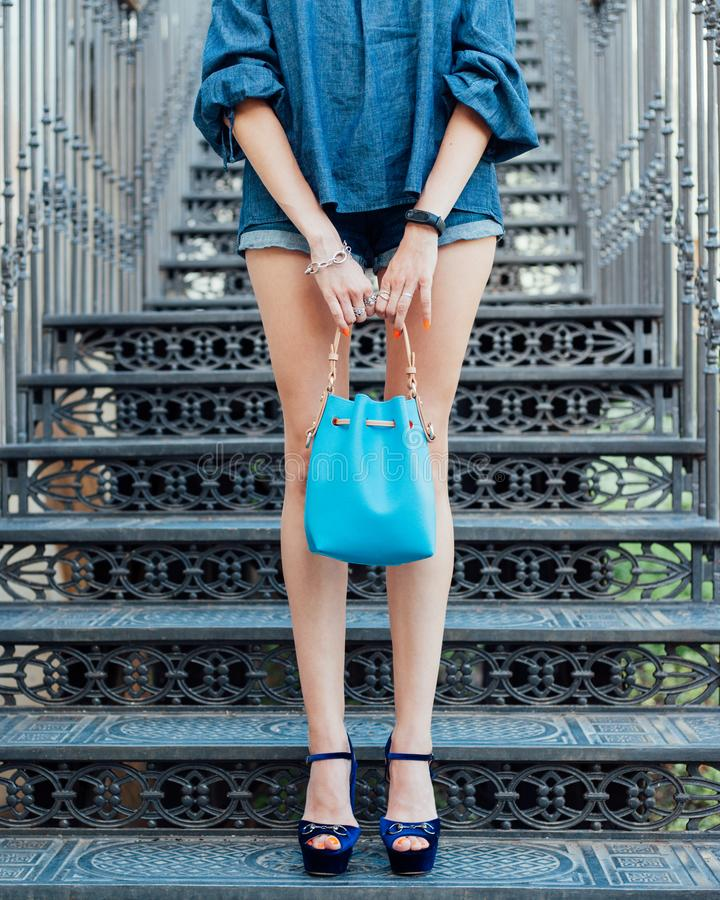 Fashion. A girl with long legs posing in high-fashioned high-heeled shoes and a blue handbag on a hot summer day, stands on the an royalty free stock images
