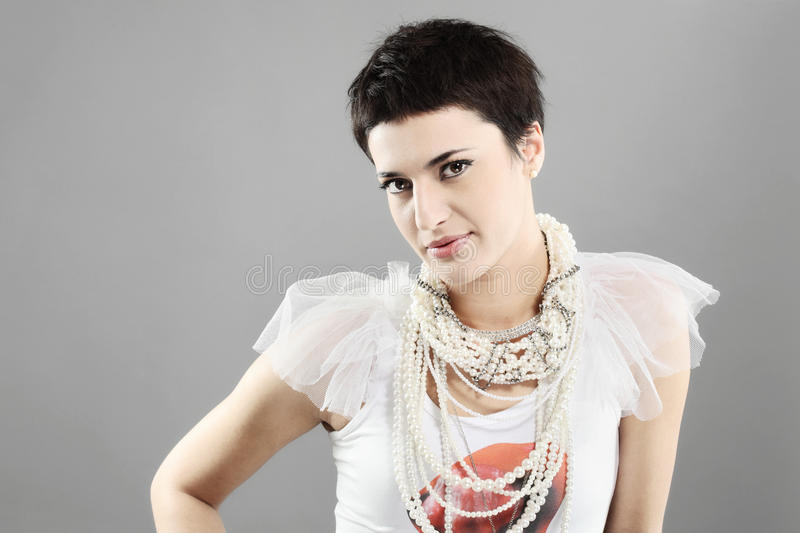 Fashion girl with pearl necklaces. Beautiful girl with short black hair, and pearl necklaces royalty free stock photos
