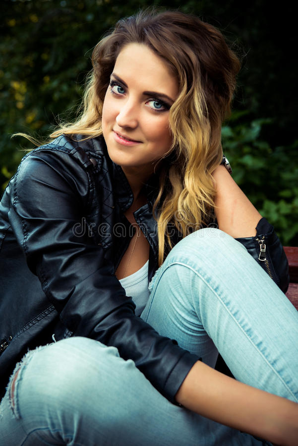 Fashion girl posing with leather jacket stock images