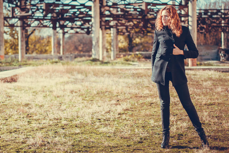 Fashion girl with red hair. Girl with red hair stands against an old reinforced concrete construction stock photos