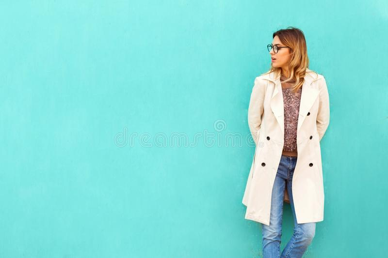fashion girl in round glasses stands posing near a turquoise wall stock photo