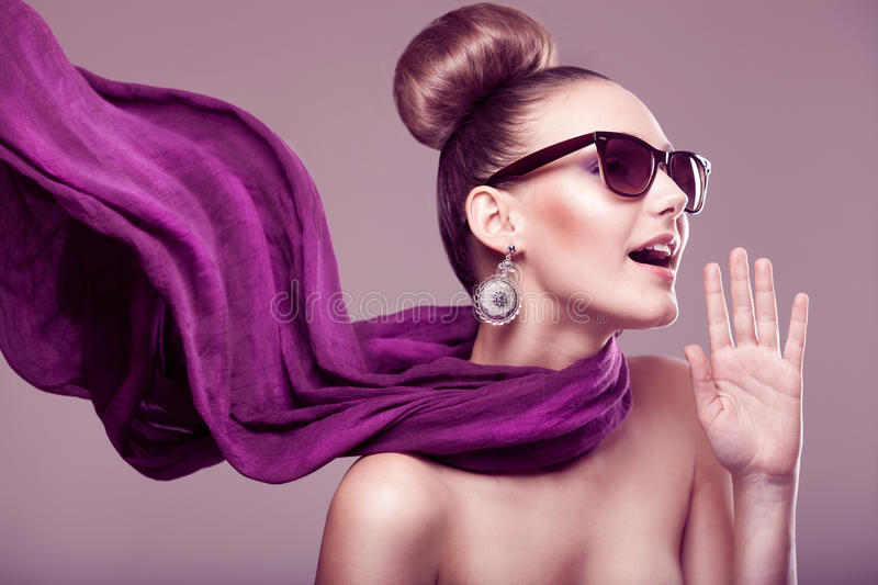 Fashion girl with a scarf. Fashion girl with a purple scarf, wearing sunglasses, updo