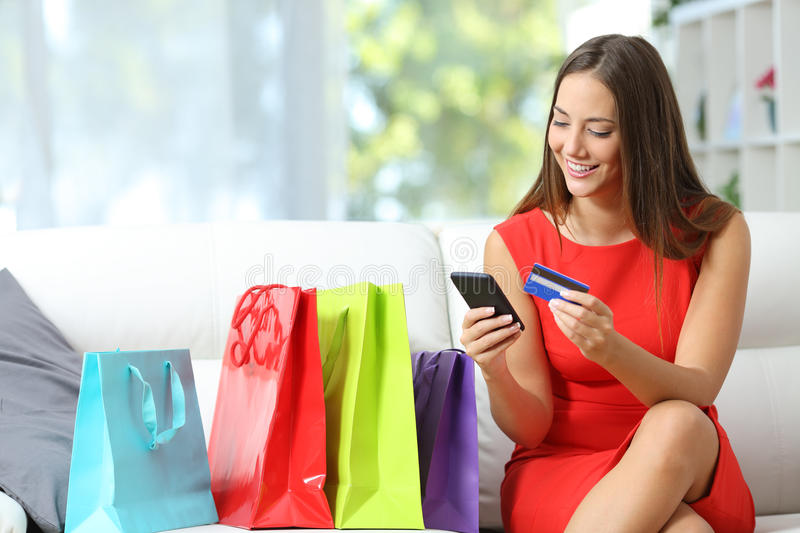 Fashion girl shopping online with bags beside. Fashion girl buying online with smart phone and credit card with colorful shopping bags beside