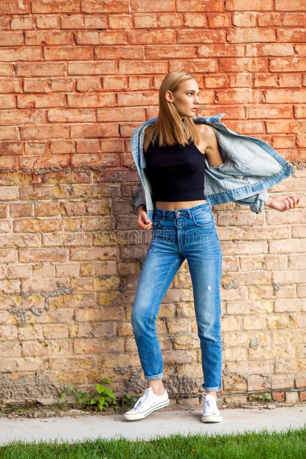 fashion girl standing near brick wall in denim and sneakers. Vogue Style stock images