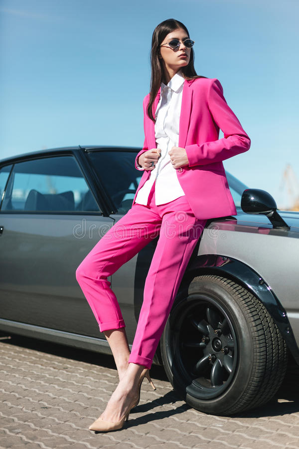 Fashion girl standing next to a retro sport car on the sun. Stylish woman in a pink suit waiting near classic car royalty free stock photo