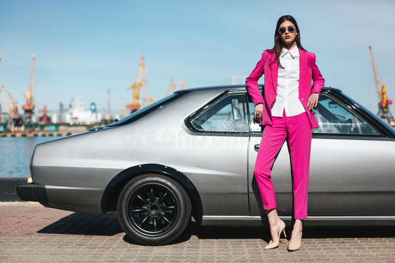 Fashion girl standing next to a retro sport car royalty free stock photography
