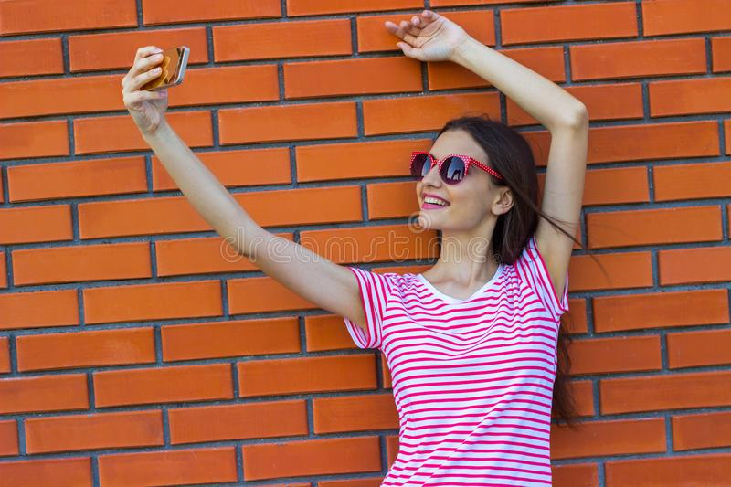 Fashion girl taking self-portrait on smartphone in city over red brick wall background.  royalty free stock images