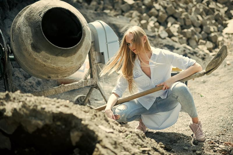 Fashion girl work at construction, vogue. Woman worker in shirt and jeans on building site, fashion. Woman with long royalty free stock image