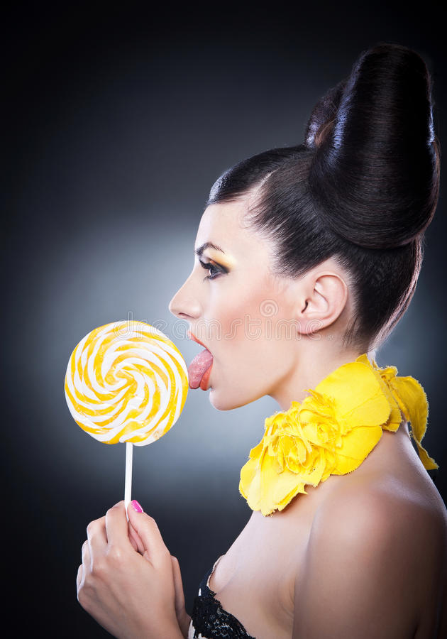 Fashion girl with yellow lollipop and smile against a background. Portrait of beautiful woman with beauty hair licking lollipop royalty free stock photography