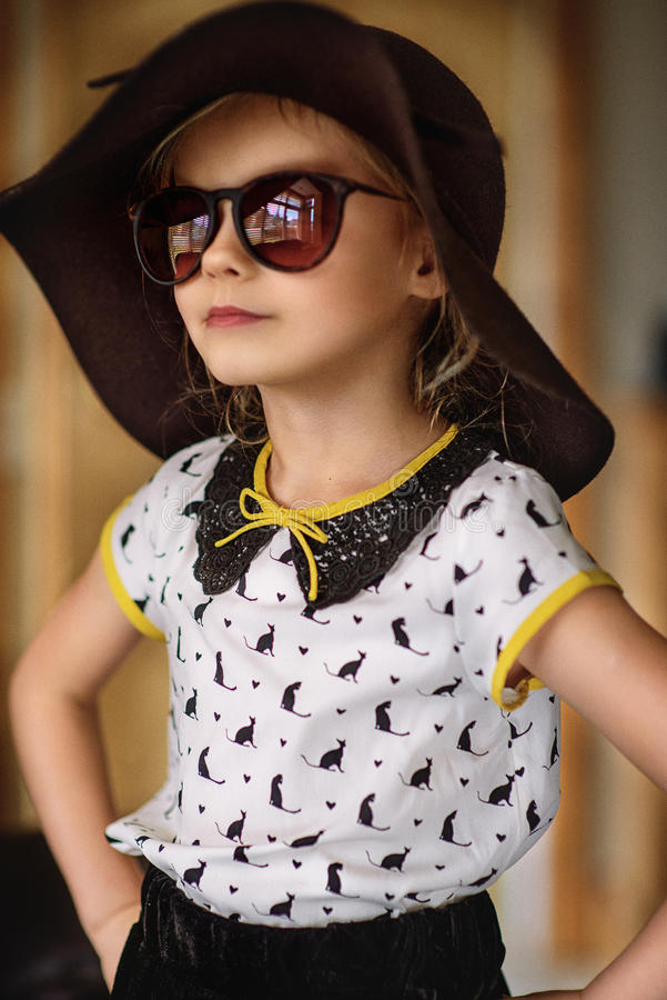 Fashion Girl. A young girl wearing sunglasses and a hat royalty free stock images