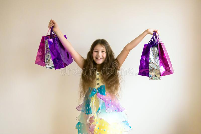 Beautiful smiling little girl with shopping bags and gifts. royalty free stock photo