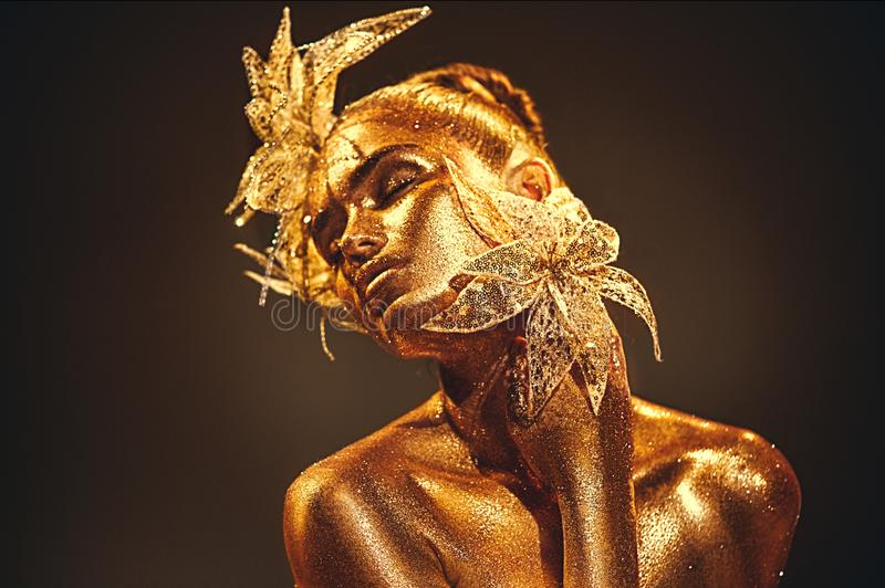 Fashion gold model woman with bright golden sparkles on skin posing, fantasy flower. Portrait of beautiful girl with glowing makeu royalty free stock photo