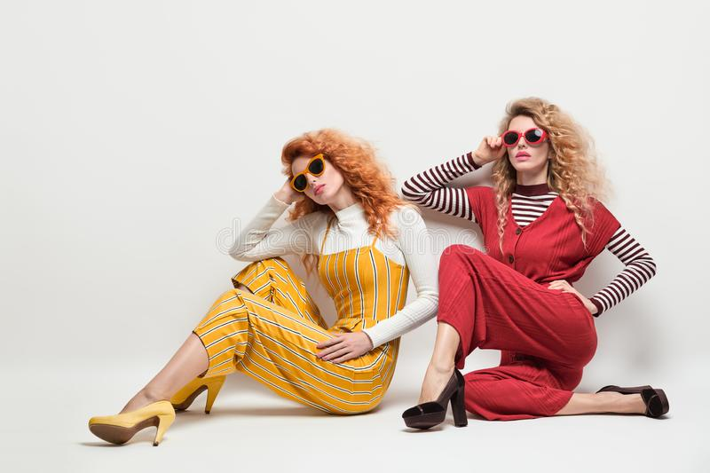 Two Gorgeous Girl in Fashion Outfit. Curly Hair royalty free stock image