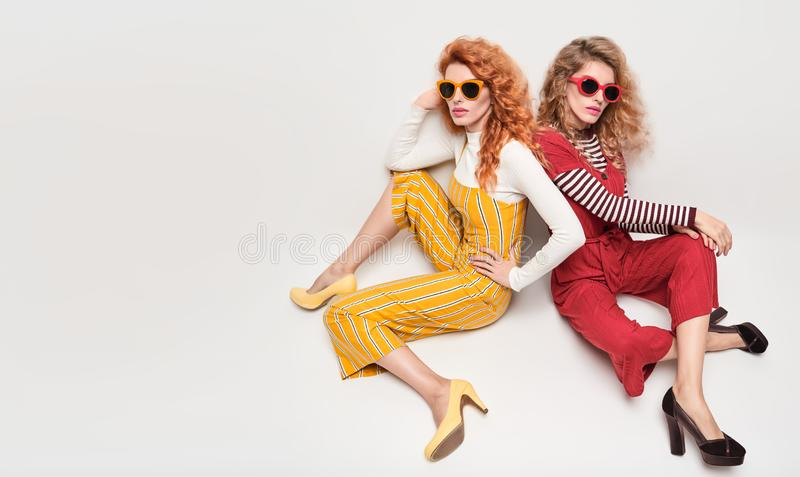 Two Gorgeous Girl in Fashion Outfit. Curly Hair royalty free stock images