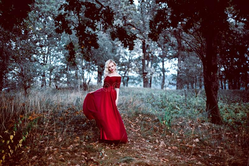 Fashion gorgeous young blonde woman in beautiful red dress in a fairy-tale forest. magic atmosphere. Retouched toning shot royalty free stock image