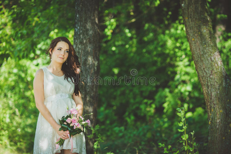Fashion gorgeous young blonde woman in beautiful white dress in a fairy-tale forest. magic atmosphere stock images