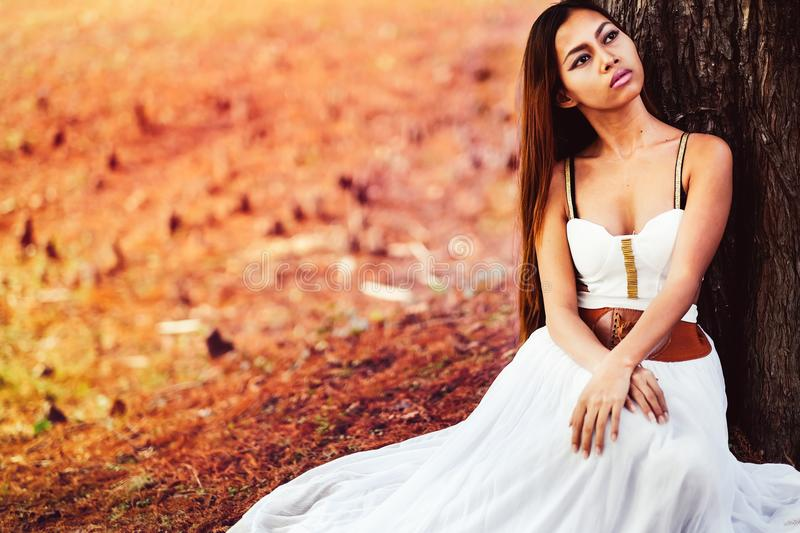 Fashion gorgeous young woman in beautiful white dress sitting on the ground in a fairy-tale forest royalty free stock photo
