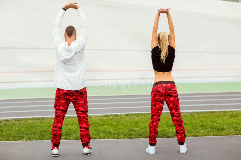 Fashion guy with a girl posing in the same sportswear. Couple playing sports royalty free stock image