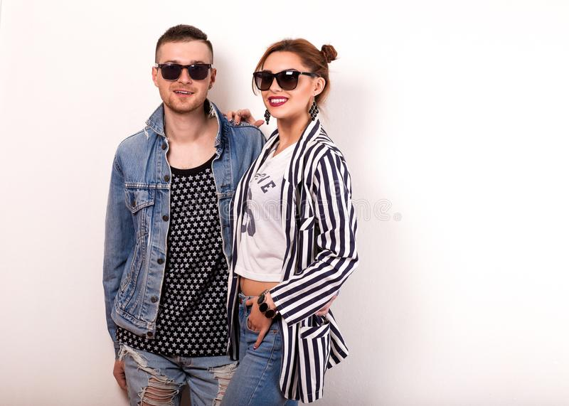 Fashion guy with a girl in the studio posing on a gold backgroun. D, the guy dressed in a sweatshot with pineapple stock image