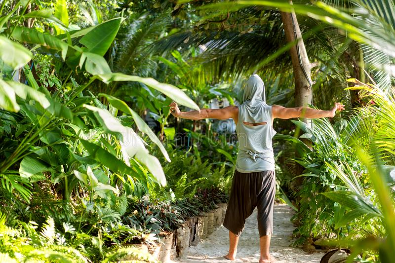 Fashion guy in the jungle is posing in his robes.  stock images
