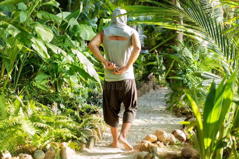 Fashion guy in the jungle is posing in his robes.  stock image