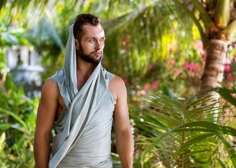 Fashion guy in the jungle is posing in his robes.  stock photography