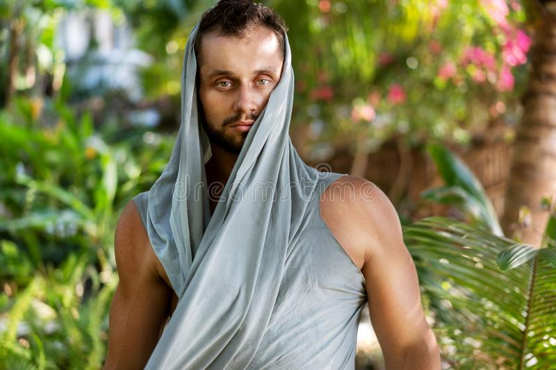 Fashion guy in the jungle is posing in his robes.  stock photo
