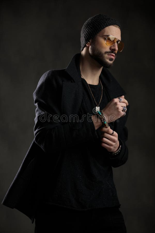 Fashion guy looking away wearing sunglasses and beanie. Fashion guy looking away wearing orange sunglasses and fixing sleeve, necklace, bracelets, rings stock image