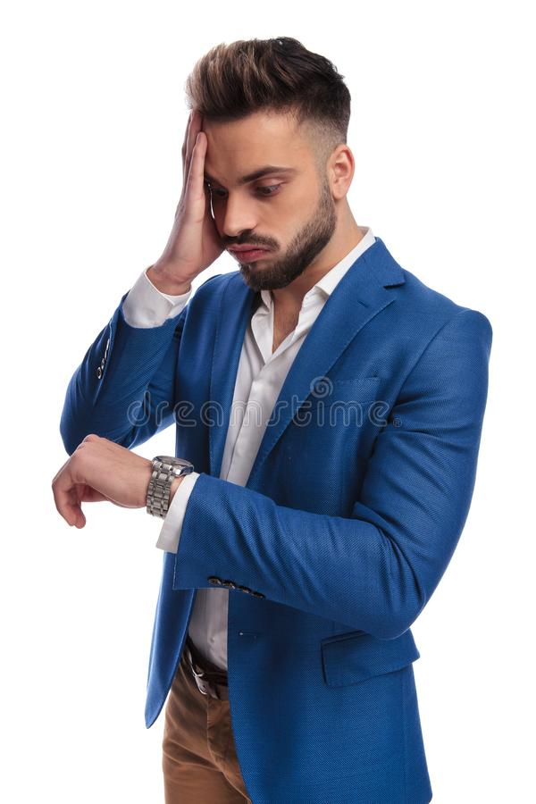 Fashion guy looking at watch running late with hand on face. Fashion guy in suit looking at his watch running late with hand on face on white background stock images