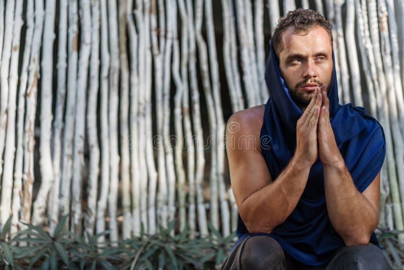 Fashion guy makes namaste near bamboo white background, prays royalty free stock image