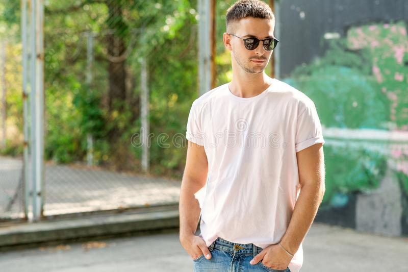 Fashion guy posing outdoors in sunglasses.  stock images