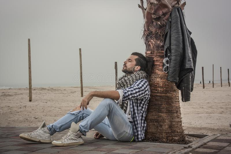 Fashion guy sitting by the sea. Near a palm stock photography