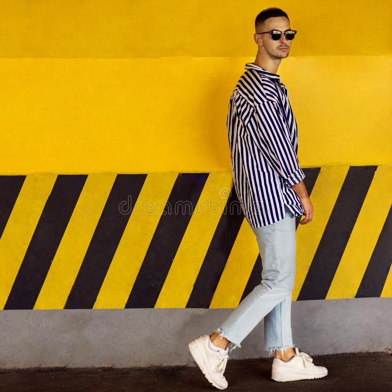 Fashion guy in a striped shirt is standing near a yellow parking. Wall royalty free stock images
