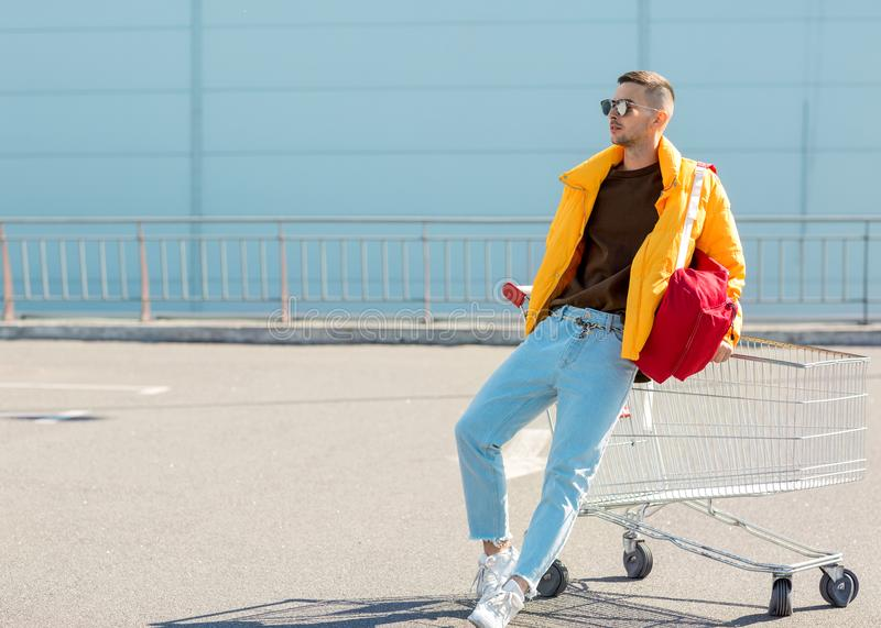 Fashion guy in sunglasses and a yellow jacket jump in a cart fro. M food in the supermarket parking stock photo