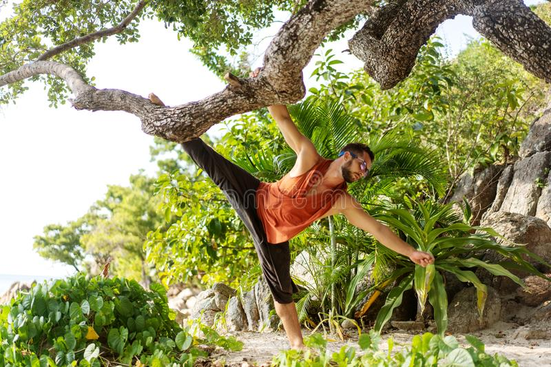 Fashion guy in tropical palms doing acrobatics.  stock images