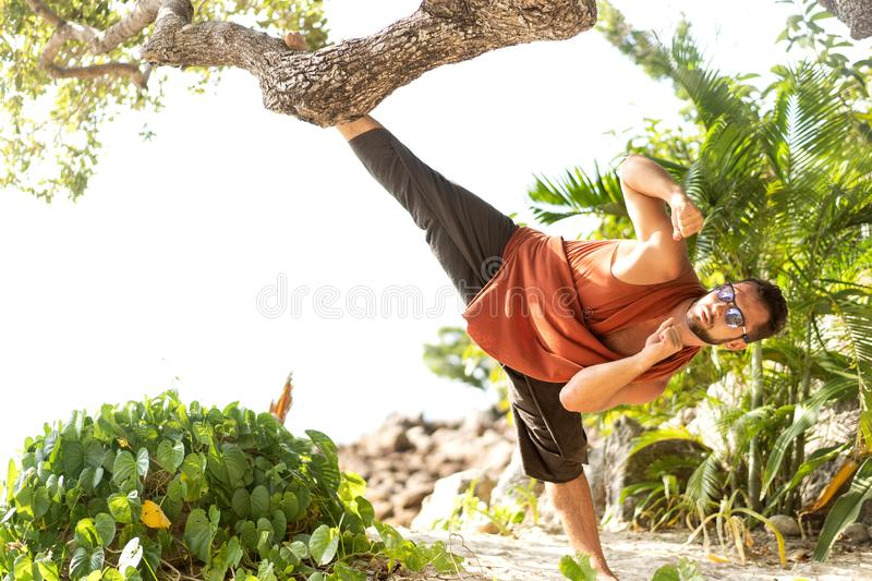 Fashion guy in tropical palms doing acrobatics.  royalty free stock image