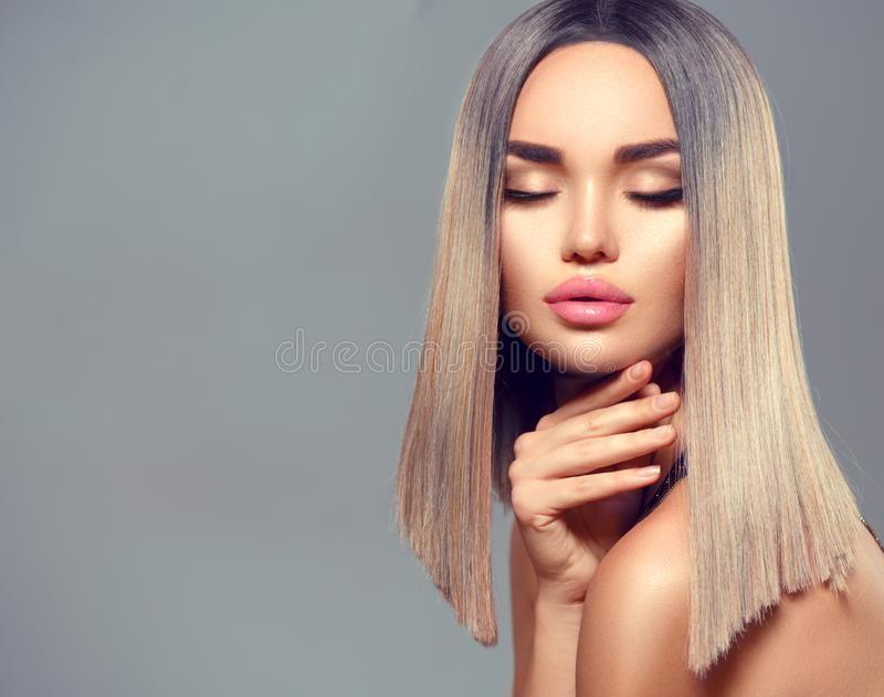 Fashion hairstyle. Ombre dyed hair. Beauty Model girl with perfect healthy hair and beautiful makeup posing in studio royalty free stock image