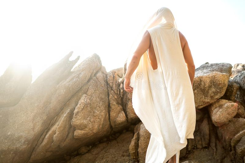 Fashion handsome guy at sunset posing in a white robe near the rocks.  royalty free stock photo