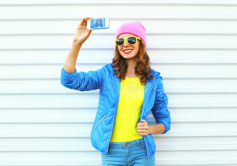 Fashion happy cool smiling girl in colorful clothes taking picture makes self portrait on smartphone over white background royalty free stock photos