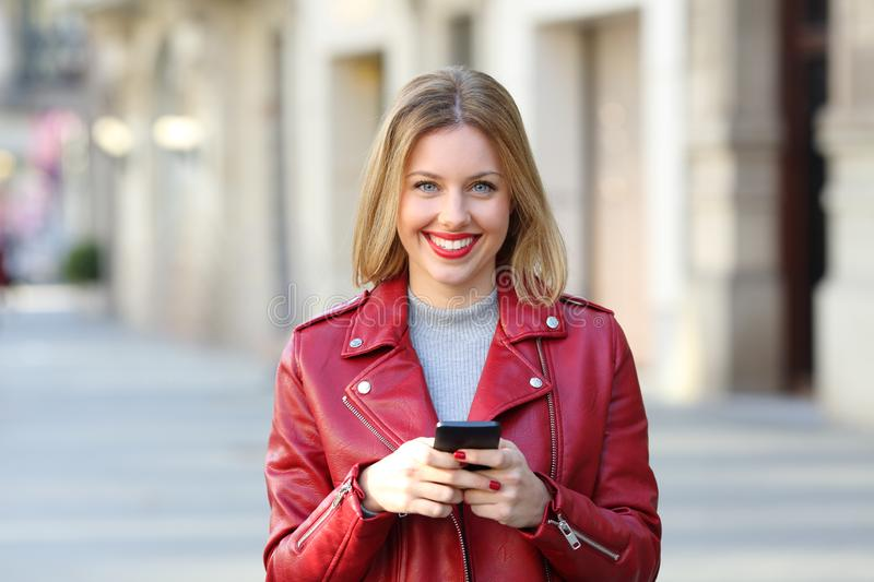 Fashion happy girl looks at camera holding phone. Fashion happy girl looks at camera holding a smart phone in the street stock photos
