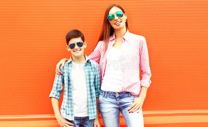 Fashion happy mother with son teenager in a sunglasses, checkered shirts stock images