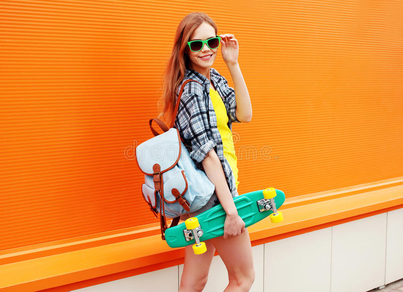 Fashion happy smiling hipster cool girl in sunglasses with skate royalty free stock photography