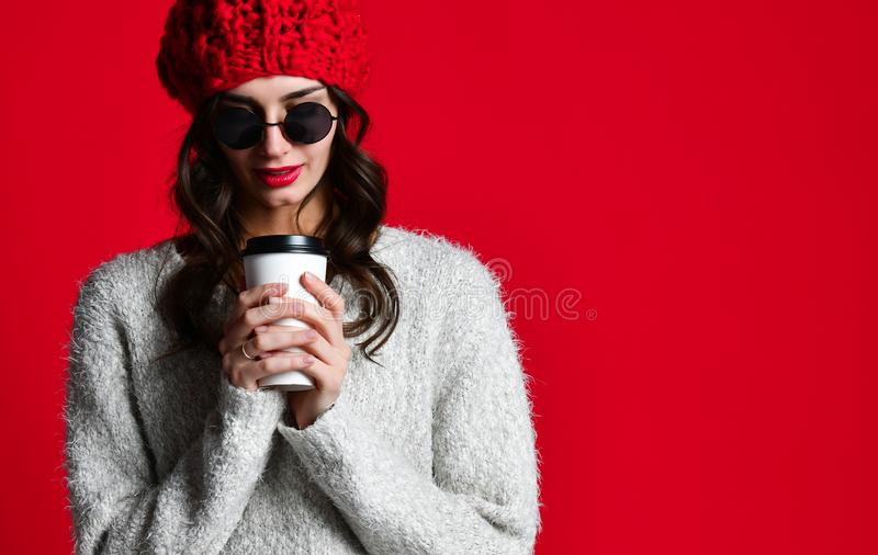 Fashion happy smiling woman holds coffee cup on red wall background royalty free stock photos
