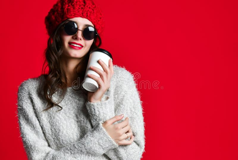 Fashion happy smiling woman holds coffee cup on red wall background stock photo