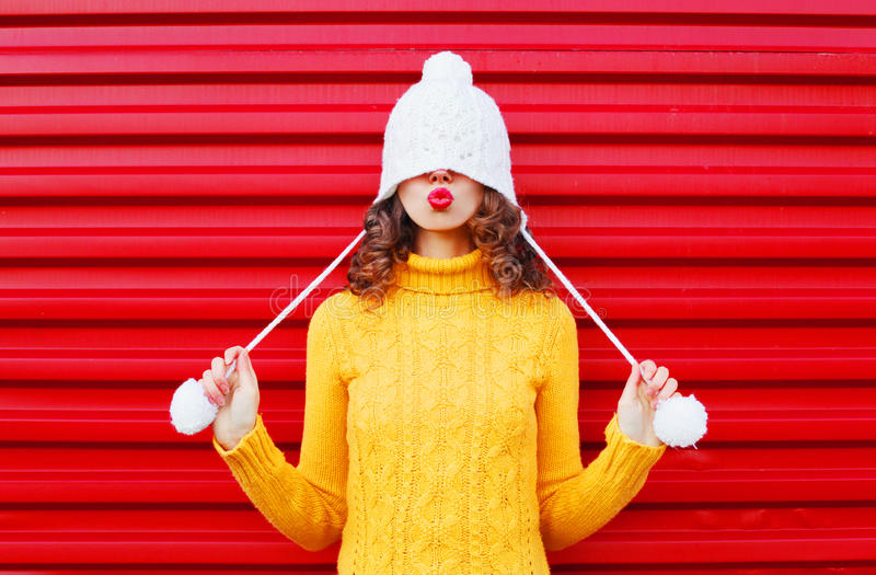Fashion happy woman blowing red lips makes air kiss wearing colorful knitted hat, yellow sweater over red. Background stock photos